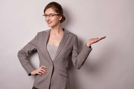 A girl in a gray jacket and glasses stands on a white background, looks at the camera, pointing his palm to the side. Фото со стока