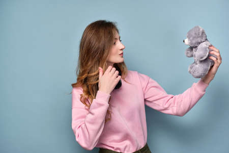 A girl in a pink sweater stands on a blue background and looks at a bear toy in her hand and looks at him.