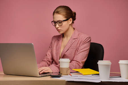 Red-haired girl in a jacket and glasses sits at a table half a turn and prints on a laptop.