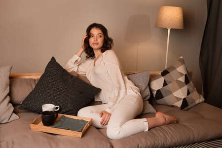 A curly dark-haired girl sits on a sofa with a tray with mugs, legs crossed and looks to the side. Stockfoto - 129234129