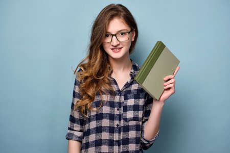 A young girl in a plaid dress and glasses stands on a blue background with a book in her hands and looks at the camera. Фото со стока - 129234132