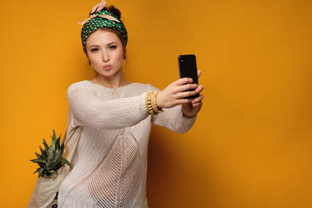 A redhead girl with a bright scarf on head is standing on an orange background and taking a selfie, looking at the camera Zdjęcie Seryjne - 129234131