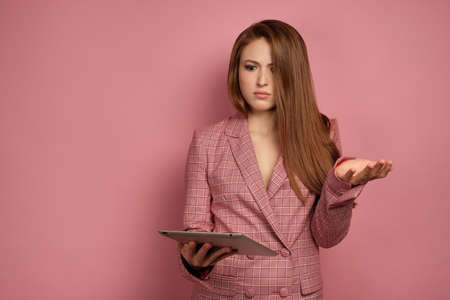 Red-haired girl in a jacket stands on a pink background with incomprehension looking into an electronic tablet.