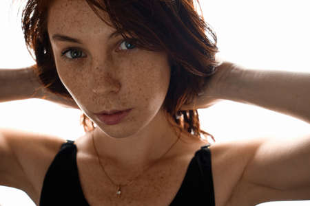 Red-haired girl with freckles looks in the frame, collecting hair with her hands, standing in the sun.