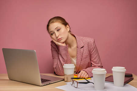 Red-haired girl in a jacket sitting at a table in front of a laptop on a pink background, his head on his hand, falling asleep.