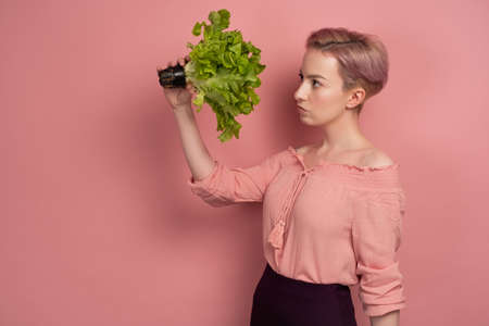A girl with short pink hair in a blouse looks thoughtfully at a salad in her hand, standing in profile on a pink background.