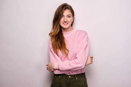 A girl in a pink sweater stands on a white background, hugging herself with her arms and smiling at the camera.