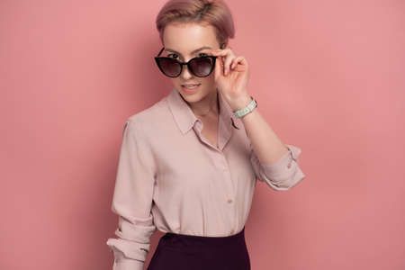 A girl with short pink hair in a blouse and skirt stands on a pink background, looking over sunglasses. Imagens