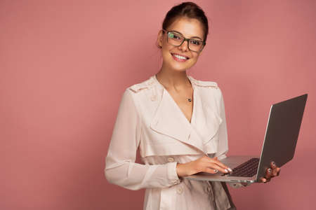 A dark-haired girl in a light jacket and glasses stands with a laptop in her hands on a pink background and smiles at the camera. Фото со стока - 129234141