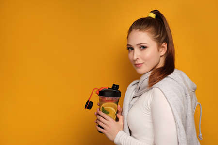 Red-haired girl standing on a half-turn on a yellow background with a sports shaker and looking at the camera.
