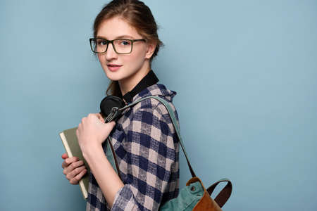 A girl in a plaid shirt and glasses with headphones on her neck stands on a blue background in profile with a book and a backpack.
