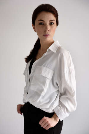 A red-haired girl in a white shirt and black trousers stands in a half-turn on a white background and looks at the camera.