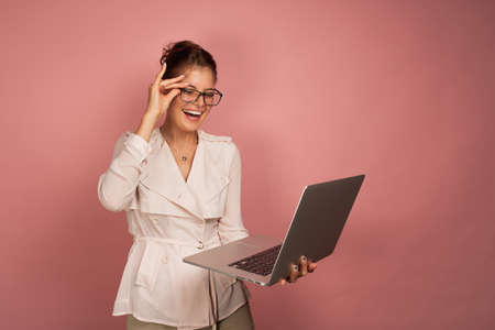 A brunette stands on a pink background with her hair collected and happily looks into the laptop while adjusting her glasses.