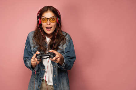 Brunette on a pink background in jeans, glasses and headphones in amazement looking forward, holding a game console. 스톡 콘텐츠