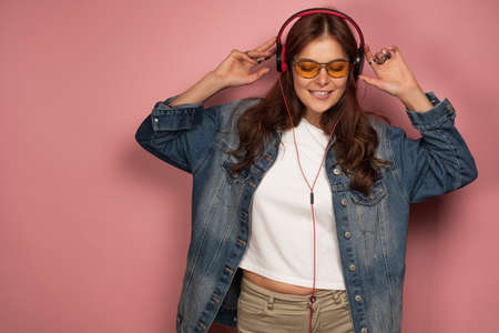 A girl in a jeans stands on a pink background in headphones and glasses with her eyes closed and biting her lip listens to music