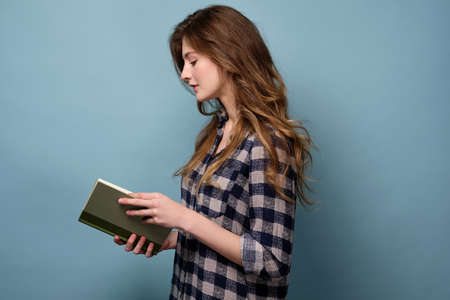 A young girl in a plaid shirt stands in profile on a blue background and looks down at the book with his head bowed.