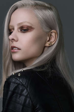 Portrait of a platinum blonde with bright bronze eye makeup.