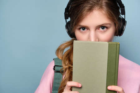 A young girl in a pink sweater and headphones with a backpack stands on a blue background and looks out from behind a book.