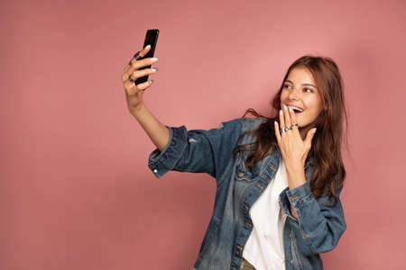 A dark-haired girl in jeans stands on a pink background with headphones on her neck and laughs and takes a selfie.