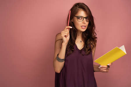 A dark-haired girl in a purple top with a notebook and pencil stands on a pink background, looking thoughtfully to the side