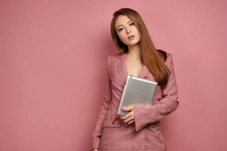 Red-haired girl in a business suit and glasses is standing on a pink background and holding a laptop and looking at the camera. Фото со стока - 129234184
