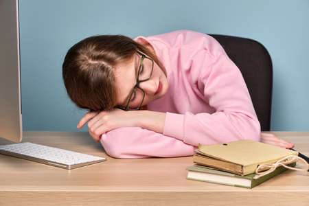 A girl in a pink sweater sits at a table with a computer and books with her head resting on folded hands.