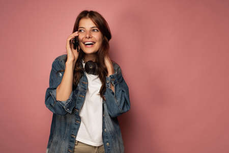 Brunette on a pink background in jeans with headphones around her neck happily smiling on the phone.