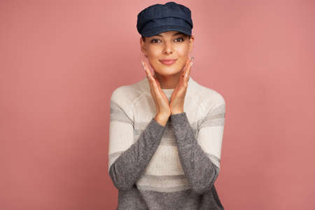 A girl in a sweater and blue cap is standing on a pink background, looking at the camera while holding palms against face Фото со стока - 129234438