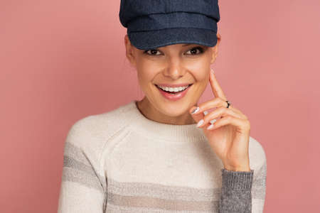 Brunette on a pink background in a blue cap and a sweater happily smiling looks at the camera.