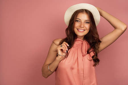 A dark-haired girl in a pink dress stands on a pink background and holding a straw hat looks at the camera.