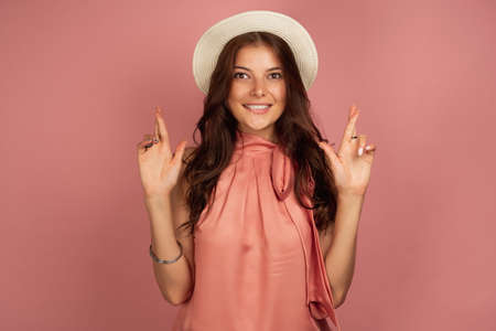 The brunette stands on a pink background in a straw hat, looks at the camera with her fingers crossed. Фото со стока - 129234447
