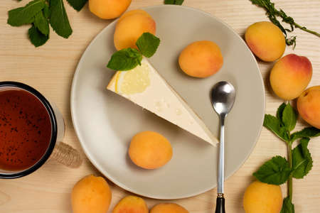 Cheesecake decorated with mint and lemon on a plate with a cup of tea is surrounded by herbs and apricots on a light wooden table Stockfoto