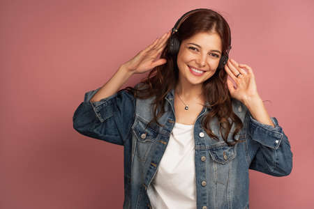 A brunette on a pink background in a denim shirt is smiling and looking into the camera while holding the headphones in her hands Фото со стока