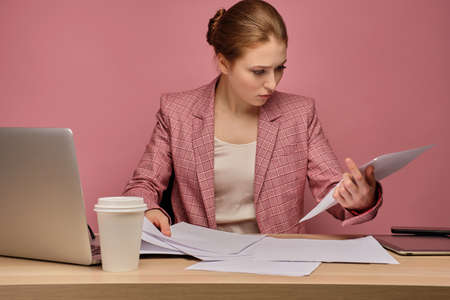 Red-haired girl in a suit on a pink background sits in front of a laptop and intensely looks at the paper.