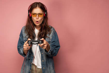 A girl in a jeans, headphones and glasses stands with a gamepad in her hands, her face stretched out in displeasure.