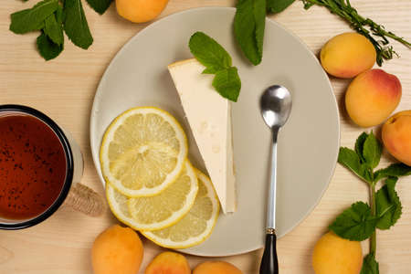 Cheesecake on a plate with a cup of tea is surrounded by herbs and apricots on a bright wooden table Stockfoto