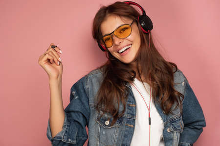 A dark-haired girl in a jeans stands on a pink background in headphones and laughs, looking at the camera, snapping her fingers