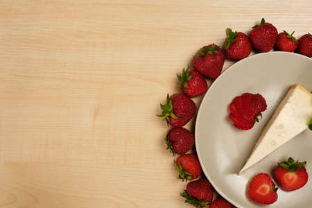 A plate with cheesecake stands in a frame of strawberries with the edge of the frame on a light wooden table.