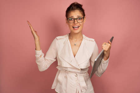 A girl in a light jacket and glasses stands on a pink background with a laptop and spreads her arms to the side, raising eyebrows