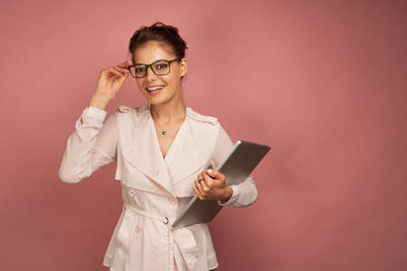 A brunette stands on a pink background with the collected hair holding a laptop in her hand and points her glasses at the camera. 스톡 콘텐츠