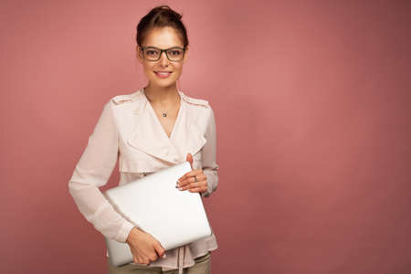 A dark-haired girl in a light jacket stands on a pink background with a laptop in her hands and looks at the camera. 스톡 콘텐츠