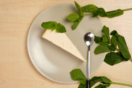 Cheesecake on a plate is surrounded by herbs on a light wooden table