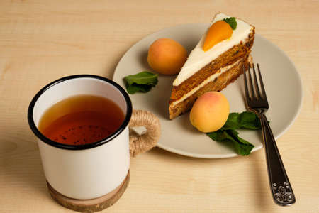 Plate with carrot cake and apricots stands with a cup of tea on a light wooden table.