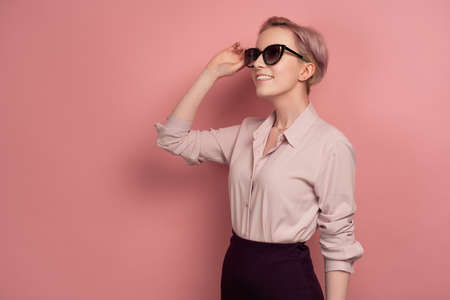 A girl with short pink hair in a blouse, skirt and glasses stands in a half-turn on a pink background and looks to the top.