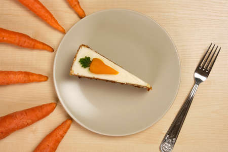Plate with a piece of carrot cake and a fork surrounded by carrots on a wooden table