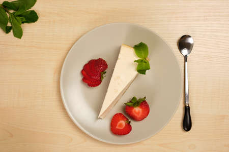 A plate with cheesecake, a spoon and strawberries stands in the middle on a bright wooden table.