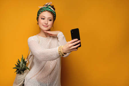 Girl in a light sweater and knotted a colored head scarf with a pineapple in a bag and takes a selfie.
