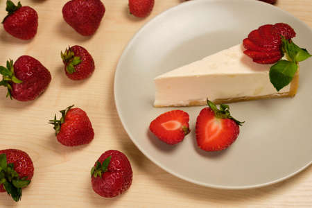 A plate with cheesecake and berries stands surrounded by strawberries on a wooden table