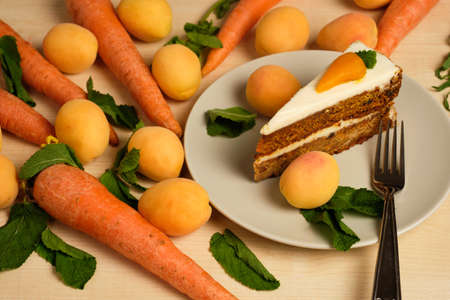 A plate with a piece of carrot cake and a fork stand surrounded by apricots and carrots on a wooden table