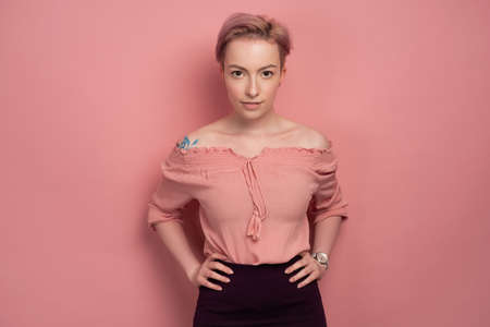 A girl with short pink hair in a blouse and a skirt stands on a pink background and looks at the camera with her hands on waist. Фото со стока